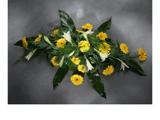Sargschmuck mit gelben Gerbera u. Lilien